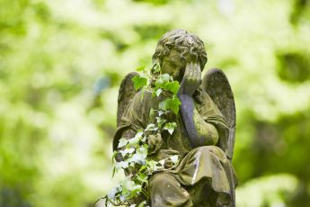 Sad angel statue on old cemetery