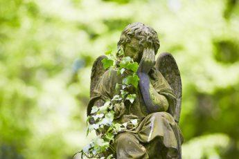 Sad angel statue on old cemetery